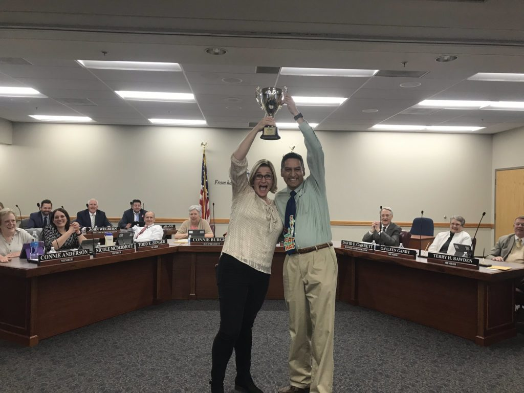 Diamond Ridge Elementary staff holding trophy at board meeting