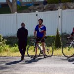 Teacher on bicycle next to police officer and superintendent
