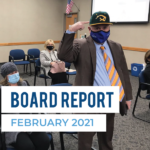 Danny Stirland points to Kearns High cap and text 'Board Report February 2021'
