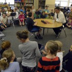 Photo of students watching a chess match between a student and Superintendent Bates