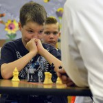 Photo of a student playing chess with Superintendent Bates